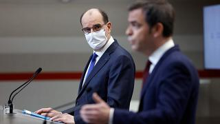 French Prime Minister Jean Castex, left, looks on as French Health Minister Olivier Veran speaks during a press conference in Paris, Thursday, Jan. 14, 2021.