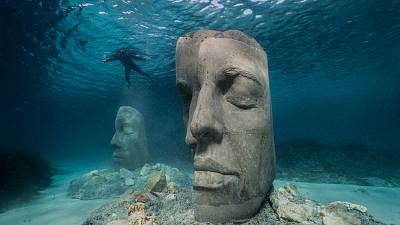 The mask-like sculptures sit on the seabed just not far from the shore.