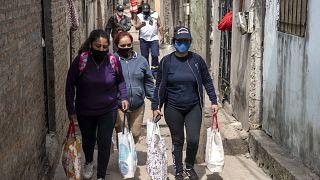 Unas mujeres llevan bolsas con raciones de comida de un comedor social para alimentar a las personas más afectadas por la crisis económica.