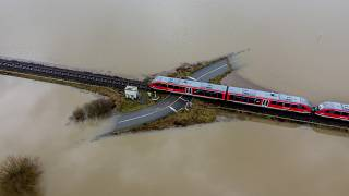 A train passes a railway crossing that is surrounded by flooding caused by rain and melting snow in Nidderau near Frankfurt, Germany. February 3, 2021