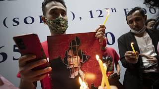 Myanmar nationals in Thailand hold pictures of Aung San Suu Kyi and lit candles during a protest in front of the Myanmar Embassy in Bangkok, Feb. 4, 2021.