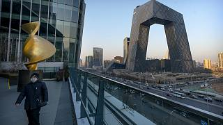 A man walks along an observation deck near the CCTV Headquarters building, the home of Chinese state-run television network CCTV and its overseas arm CGTN, in Beijing.