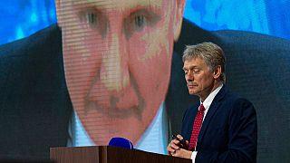 المتحدث باسم الكرملين ديمتري بيسكوف وخلفه الرئيس الروسي فلاديمير بوتين يتحدث عبر مكالمة فيديو خلال مؤتمر صحفي في موسكو ديسمبر 2020