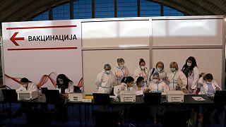 عاملون طبيون يرتدون معدات واقية يستعدون للتلقيح في مركز التطعيم المؤقت في بلغراد  25 يناير 2021