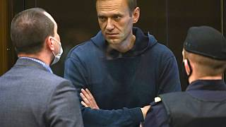 Opposition leader Alexei Navalny talks to one of his lawyers, left, before being sentenced to 3.5 years in prison