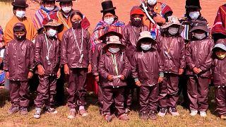 شاهد: التلاميذ في بوليفيا يرتدون بذلات تحمي من الأجسام البيولوجية للذهاب إلى المدارس