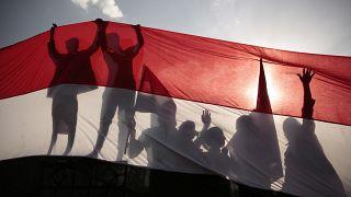 انعكاس ظل أشخاص يقفون وراء العلم اليمني خلال احتفالات سبتمبر شمال اليمن. 2016/09/26