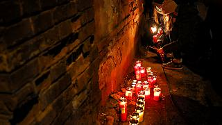 People light candles for the victims of a fire outside the Matei Bals hospital compound in Bucharest, Romania, Friday, Jan. 29, 2021.