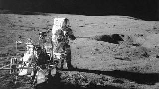Apollo 14 astronaut Alan B. Shepard Jr. conducts an experiment near a lunar crater, using an instrument from a two-wheeled cart carrying various tools.