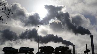 دخان يتصاعد من مصنع بينما تعبر شاحنة محملة بالسيارات جسرًا في باريس ، فرنسا.