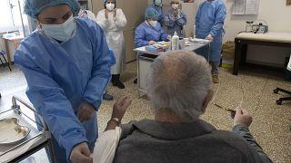 Un anziano mentre gli viene somministrata una dose di vaccino anti Covid, Roma