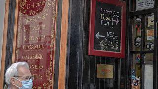 Un hombre con mascarilla pasa por delante de un establecimiento de bebidas abierto.