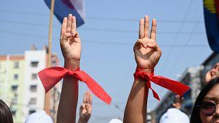 Manifestantes usam fitas vermelhas, cor do partido de Aung San Suu Kyi e fazem a saudação da resistência