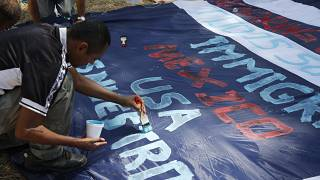 A Central American migrant paints a banner with messages in support of a migrant caravan trying to reach the US at Tecun Uman, Guatemala on the Mexican border, Jan. 22, 2020.