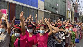 In this image made from video, protesters flash the three-fingered salute while they gather to march Saturday, Feb. 6, 2021, in Yangon, Myanmar.