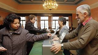 Women cast their ballots during the Federal Parliament elections 21 October 2007 at a polling station in Bulle, Switzerland.