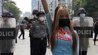 Protester posing for a photo in front of riot police line while holding a three-finger salute.