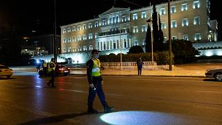Policeman at checkpoint where drivers are asked to present their movement permits, in Athens, Saturday, Feb. 6, 2021