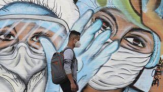Un peatón pasa junto a un mural que promueve el uso de mascarillas protectoras para ayudar a frenar la propagación del COVID-19 en Quito, Ecuador.