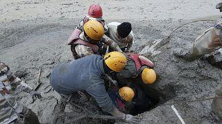 Retter klettern in ein Schlammloch auf der Suche nach Vermissten