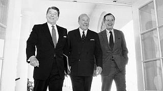 جرج شولتز وزیر خارجه وقت بین جرج بوش پدر، معاون رئيس جمهوری وقت (سمت راست) و رونالد ریگان، رئيس جمهوری وقت (سمت چپ) ایستاده است