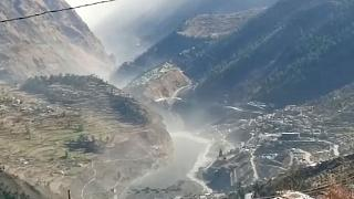 A still from video provided shows a massive flood of water, mud and debris flowing at Chamoli District