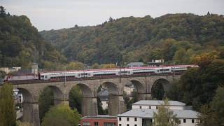 A train passes over a stone bridge in Luxembourg.