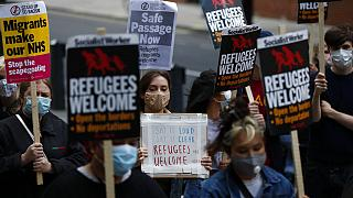 Protestors hold placards during a pro-migrants protest outside the government's Home Office in London, Tuesday, Aug. 25, 2020