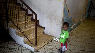 In this June 28, 2018 photo, a boy stands next to a staircase while looking out from the Nest of Hope orphanage in Port-au-Prince, Haiti.