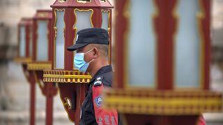 ضابط أمن يرتدي كمامة أمام معبد السماء في بكين، الصين.