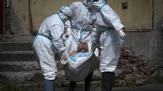 In this June 3, 2020 photo, medical workers carry a patient at infectious diseases hospital where patients with coronavirus are treated in St.Petersburg, Russia.