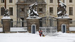 A worker cleans off snow in front of the Prague Castle after a heavy snowfall in Prague, Czech Republic.