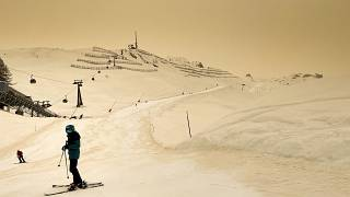 Skiers wearing protective face mask ski as Sahara sand colours the snow and the sky in orange in Anzere, Switzerland, on February 6 2021.