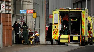 A patient is wheeled in on a trolley after arriving in an ambulance outside the Royal London Hospital in east London, Thursday, Feb. 4, 2021.
