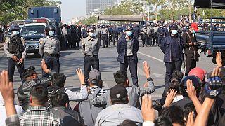 متظاهرون يقفون أمام عناصر الشرطة التي أغلقت الطريق في ماندلاي. 2021/02/09