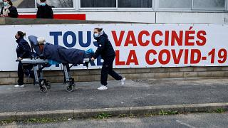 A woman is carried on a stretcher to the Covid-19 vaccination center of the South Ile-de-France Hospital Group in Melun, in the outskirts of Paris, Feb. 8, 2021.