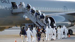 Un grupo de migrantes sube el avión del Ejército chileno en el que han sido deportados.