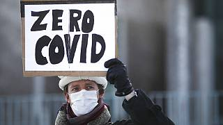 A demonstrator holds up a poster that reads: 'Zero COVID' in front of the chancellery in Berlin, Wednesday, Germany, Feb. 10, 2021, as he attends a protest.