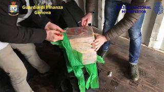 ضباط الشرطة الإيطالية يفتحون حقيبة مليئة بعبوات الكوكايين- أرشيف