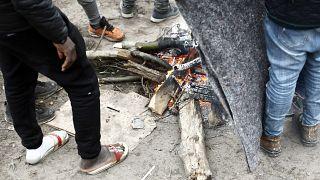Des exilés se réchauffant au coin du feu dans un camp de fortune, à Calais, dans le nord de la France, le 31 janvier 2020.