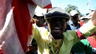 Demonstrator holds a copy of the Haitian Constitution wrapped in an American flag