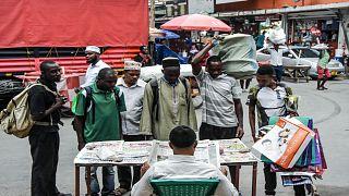 موطنون تنزانيون يقفون أمام بائع جرائد من دون التقيد بإجراءات التباعد الاجتماعي للحد من انتشار فيروس كورونا
