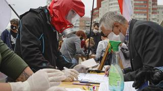 In this file June 14, 2020 photo, people, wearing face masks to protect against coronavirus, sign to support potential presidential candidates in Minsk, Belarus.