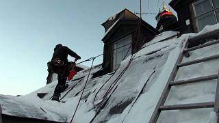 Roofer clearing snow