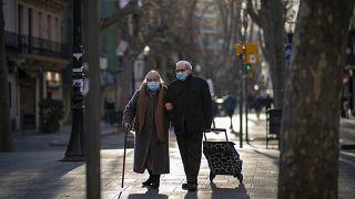 Una pareja con mascarillas camina por un bulevar en Barcelona, España, el 27 de enero de 2021.