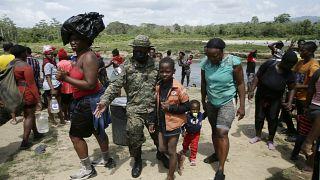 Migrantes son recibidos por un oficial de la policía fronteriza panameño en la localidad de Bajo Chiquito en Darién, Panamá, el 10 de febrero de 2021.