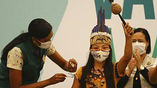 Brezilya'da geleneksel olarak giyinmiş Witoto kabilesi üyesi yerli bir kadın aşı yaptırırken.
