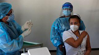 Nurse Cristina Chango receives her first dose of the Pfizer-BioNtech vaccine against COVID-19 at the Pablo Arturo Suarez Hospital in Quito, Ecuador, Thursday, Jan. 21, 2021.