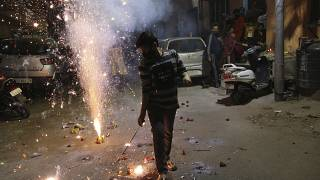 A boy plays with fireworks during Diwali, the Hindu festival of lights, in Jammu, India Saturday, Nov. 14, 2020.