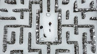 People walk with their dogs in a snow-covered garden maze in Gelsenkirchen, Germany. Extreme winter weather hit the north and west of the country. February 10, 2021
